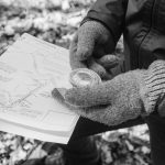 gloved hands holding a map and compass